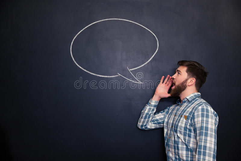 Przystojny mężczyzna krzyczy przeciw chalkboard tłu z patroszonym mowa bąblem zdjęcia royalty free