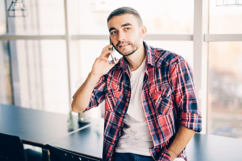 Przystojny mężczyzna mówi na telefonie w biurowych pobliskich dużych okno zdjęcia royalty free