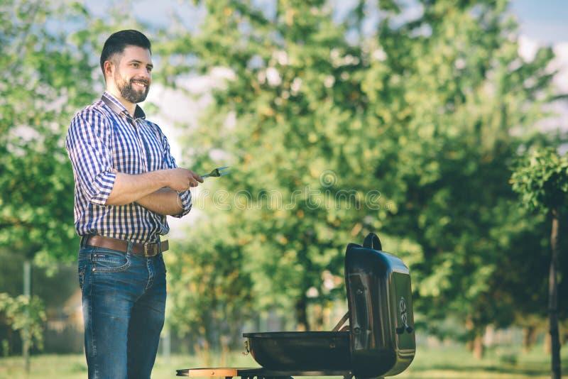Przystojny mężczyzna narządzania grill dla przyjaciół obsługuje kulinarnego mięso na grillu - szef kuchni stawia niektóre peppero fotografia stock