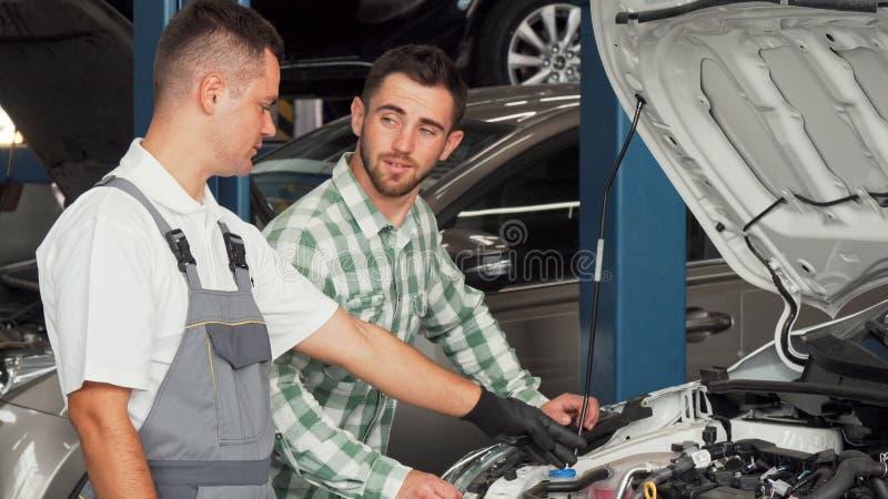 Przystojny mężczyzna opowiada samochodowy mechanik przy remontową stacją fotografia royalty free
