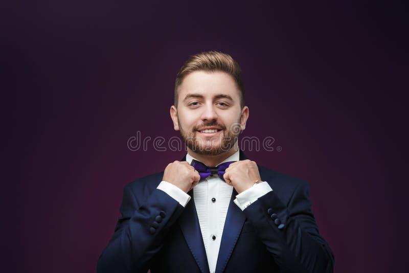 Przystojny mężczyzna patrzeje kamerę w smokingu i łęku krawacie Modna, świąteczna odzież, emcee na ciemnym tle fotografia royalty free