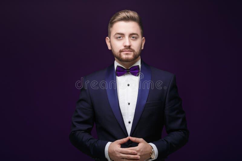 Przystojny mężczyzna patrzeje kamerę w smokingu i łęku krawacie Modna, świąteczna odzież, emcee na ciemnym tle zdjęcia stock