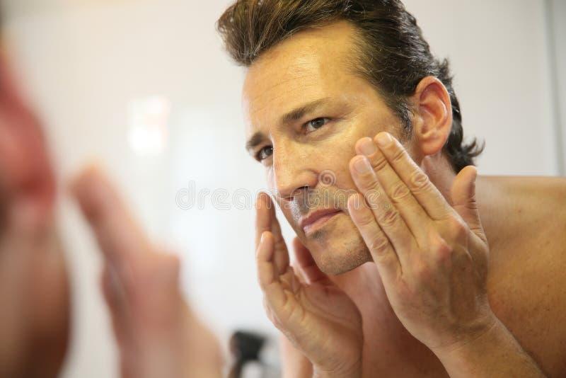 Przystojny mężczyzna patrzeje odzwierciedla myć jego twarz zdjęcia royalty free