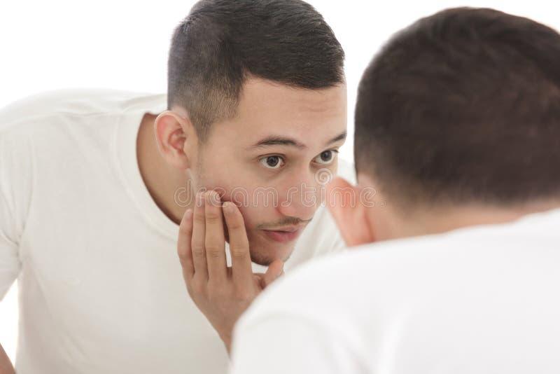 Przystojny mężczyzna patrzeje w macanie i lustro jego gładki fac fotografia stock