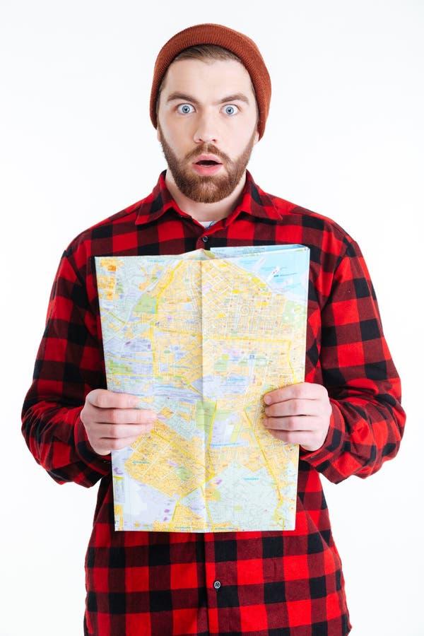 Przystojny mężczyzna patrzeje zaskakujący i trzyma mapę zdjęcia stock