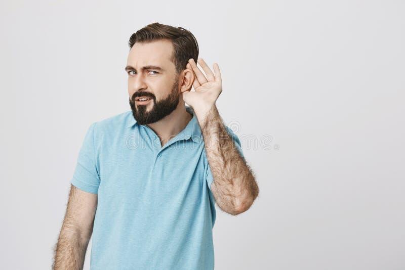 Przystojny mężczyzna patrzeje zmieszaną pozycję z ręką blisko jego ucho próbuje słuchać coś z brodą Ja jest bardzo głośny dalej fotografia stock