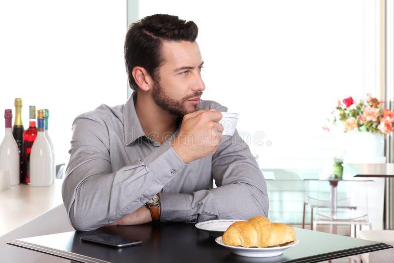 Przystojny mężczyzna pije filiżankę kawy przy barem obraz royalty free