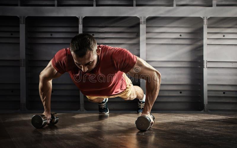 Przystojny mężczyzna podnosi ćwiczenie z jeden ręką w sprawności fizycznej gym robić pcha obraz royalty free