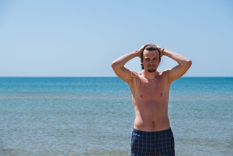 Przystojny mężczyzna pozuje na plaży, portret Ręka w włosy zdjęcia royalty free
