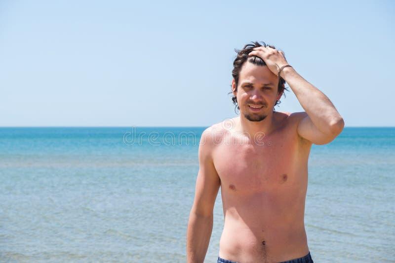 Przystojny mężczyzna pozuje na plaży, portret Ręka w włosy obraz stock