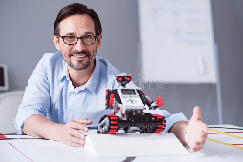 Przystojny mężczyzna pozuje z małym czerwonym robotem obraz stock
