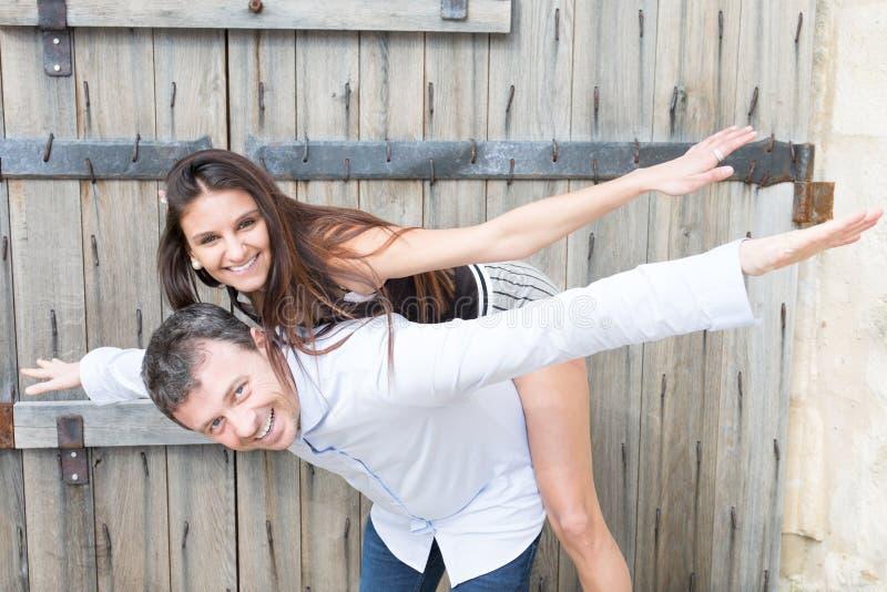 Przystojny mężczyzna robi piggyback z ładnym młodej kobiety dziewczyny napadem zdjęcia stock