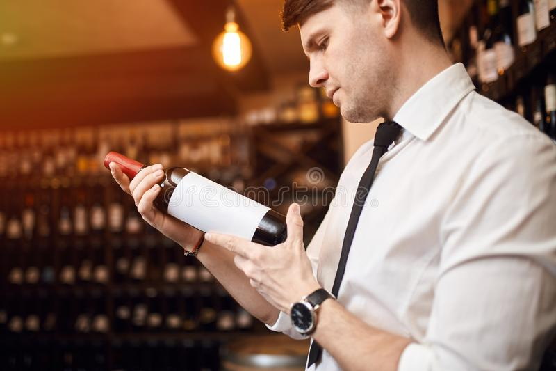 Przystojny mężczyzna rozwija technicznego i fachowego zrozumienia wino fotografia royalty free