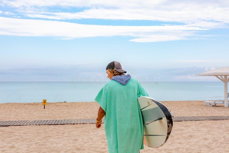 Przystojny mężczyzna spacer z białą pustą surfing deską czekać na fala surfować punkt przy dennym oceanu brzeg widok z powrotem P fotografia stock