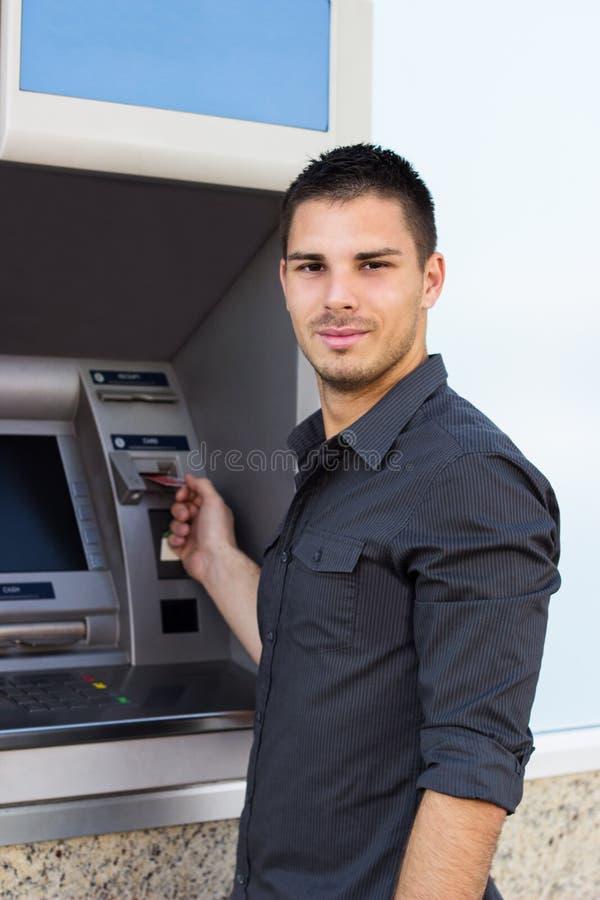 Przystojny mężczyzna stawia jego kredytową kartę przy ATM zdjęcia royalty free