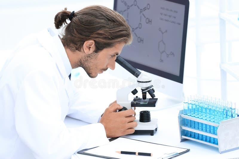 Przystojny mężczyzna technik patrzeje przez mikroskopu w lab obraz royalty free
