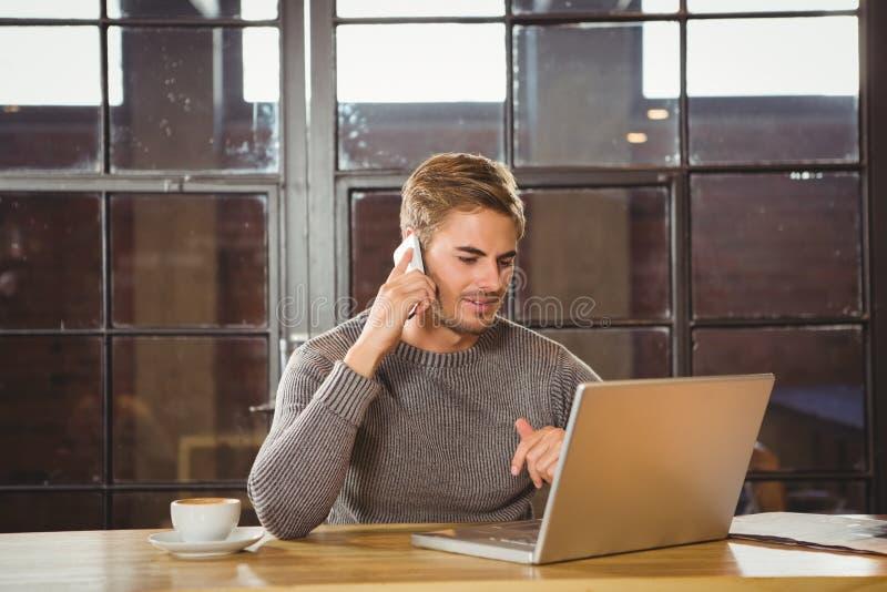 Przystojny mężczyzna telefonowanie i patrzeć laptop fotografia stock