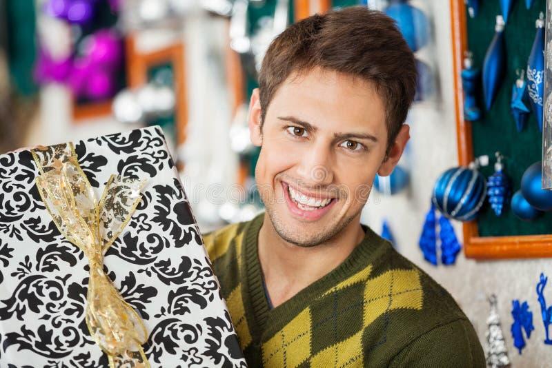 Przystojny mężczyzna Trzyma Bożenarodzeniową teraźniejszość W sklepie zdjęcia royalty free