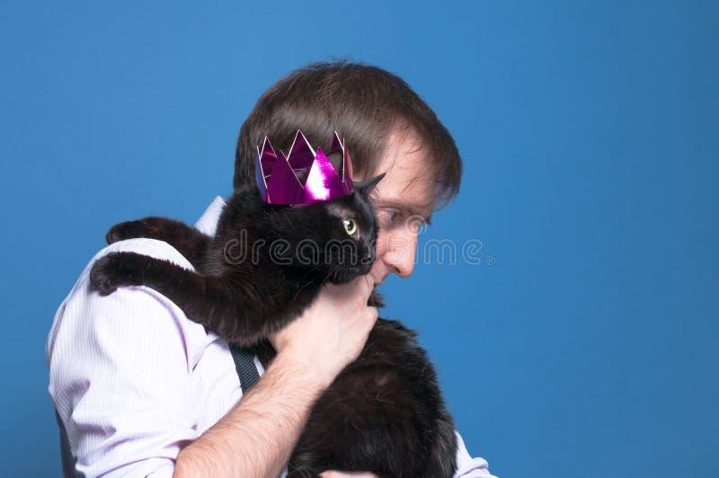 Przystojny mężczyzna trzyma dalej naramiennego czarnego kota w różowej błyszczącej koronie na błękitnym tle z kopii przestrzenią fotografia stock