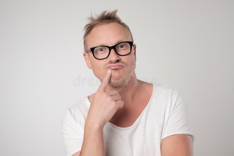 Przystojny mężczyzna trzyma rękę blisko usta w szkłach, robi planom fotografia royalty free