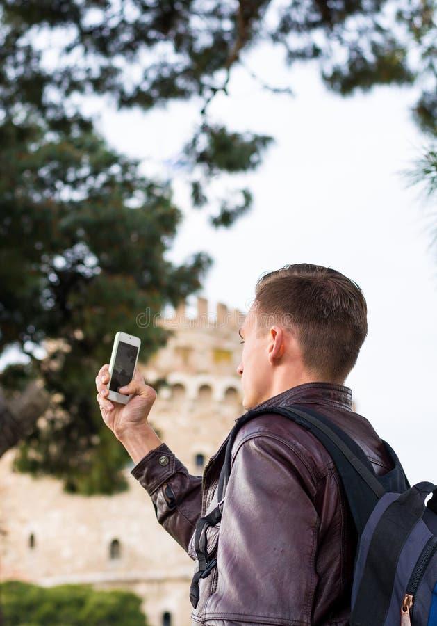 Przystojny mężczyzna, turysta, z plecakiem bierze obrazkom na smartphone Biały wierza w centrum Saloniki, Grecja obrazy stock