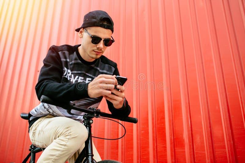 Przystojny mężczyzna używa smartphone podczas gdy siedzący na rowerze fotografia stock