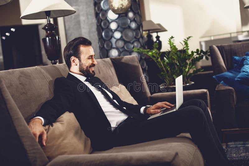 Przystojny mężczyzna używajÄ…cy laptopa w korytarzu i wyglÄ…dajÄ…cy na zadowolonego zdjęcia stock