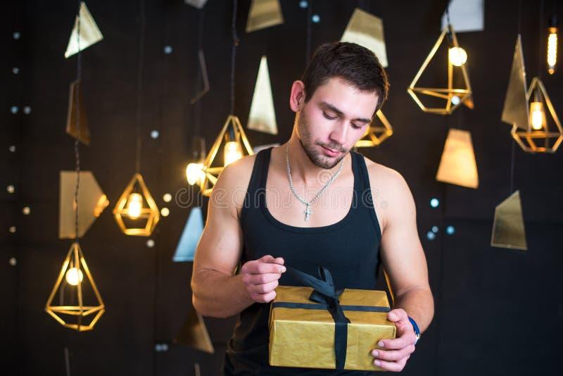Przystojny mężczyzna w czarnym podkoszulku bez rękawów trzyma prezent w jej rękach, otwiera prezent, teraźniejszość zdjęcie stock