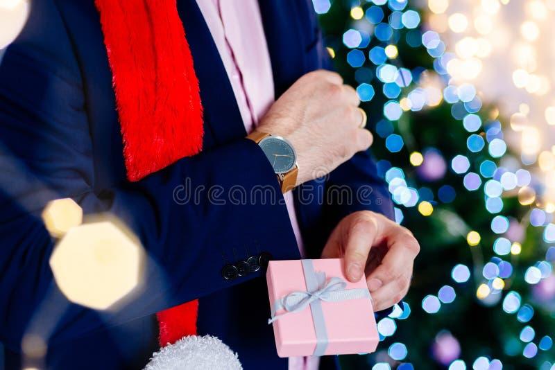 Przystojny mężczyzna w czerwonych Santa Claus bożych narodzeń mienia kapeluszowej teraźniejszości zdjęcie royalty free