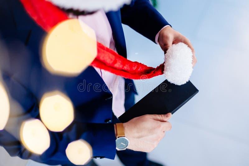 Przystojny mężczyzna w czerwonych Santa Claus bożych narodzeń mienia teraźniejszości kapeluszowym pudełku fotografia stock