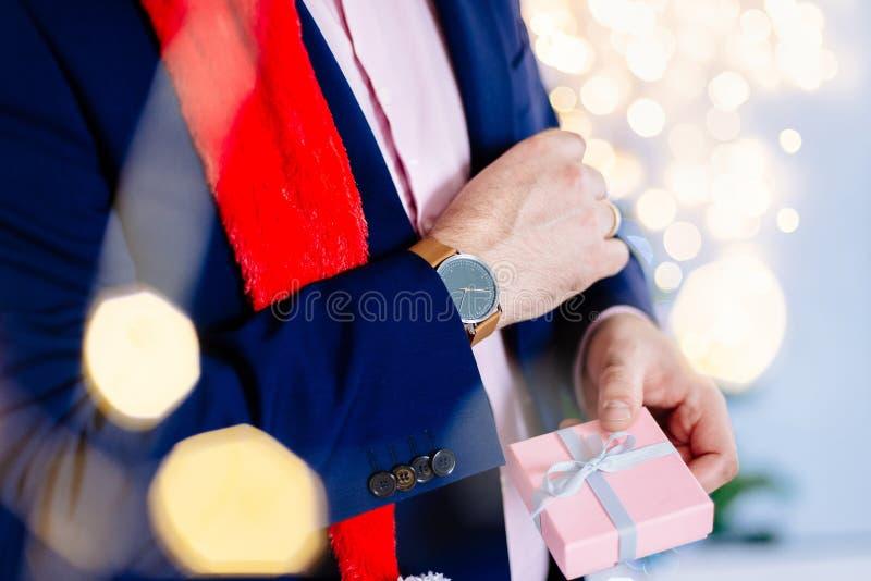 Przystojny mężczyzna w czerwonych Santa Claus bożych narodzeń mienia teraźniejszości kapeluszowym pudełku fotografia royalty free
