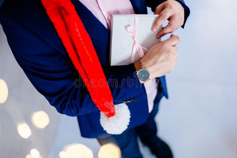 Przystojny mężczyzna w czerwonych Santa Claus bożych narodzeń mienia teraźniejszości kapeluszowym pudełku obraz royalty free