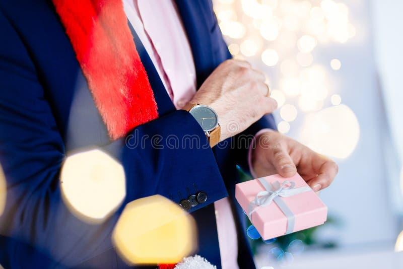 Przystojny mężczyzna w czerwonych Santa Claus bożych narodzeń mienia teraźniejszości kapeluszowym pudełku zdjęcie stock