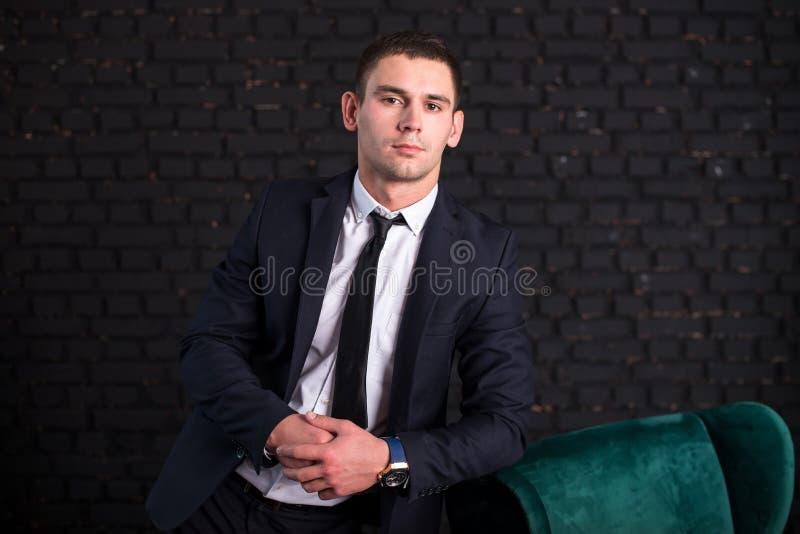 Przystojny mężczyzna w garniturze przeciw czarnemu ściana z cegieł, wzorcowa fotografia Pomyślny modny mężczyzna fotografia stock