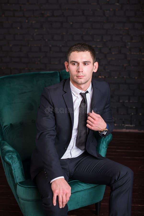 Przystojny mężczyzna w garniturze przeciw czarnemu ściana z cegieł, wzorcowa fotografia Pomyślny modny mężczyzna zdjęcia stock
