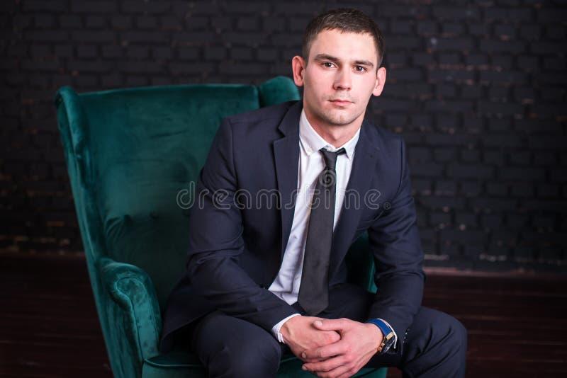 Przystojny mężczyzna w garniturze przeciw czarnemu ściana z cegieł, wzorcowa fotografia Pomyślny modny mężczyzna zdjęcie stock