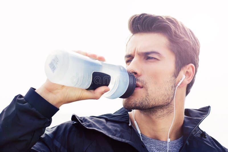 Przystojny mężczyzna w hełmofon wodzie pitnej obraz stock