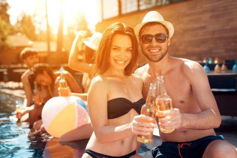 Przystojny mężczyzna w lato kapeluszu i piękny kobieta doping z piwnymi butelkami w pływackim basenie obrazy royalty free