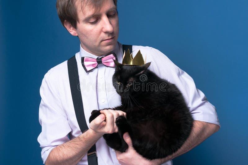 przystojny mężczyzna w mieniu i patrzeć śliczny czarny kot w złotej koronie koszula i menchia łęku krawata obraz stock
