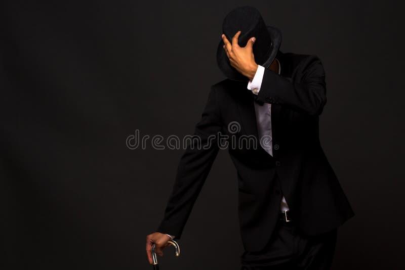 Przystojny mężczyzna w odgórnym kapeluszu pozuje z trzciną obraz royalty free