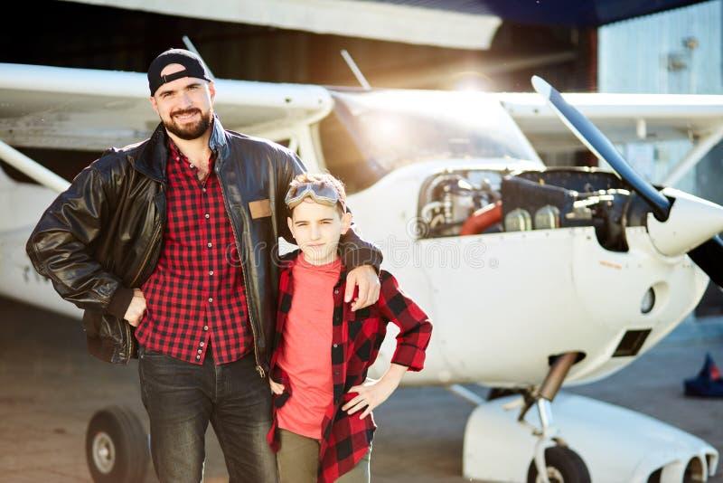 Przystojny mężczyzna w pilotowych kurtka stojakach z dzieciaka bratem blisko hangaru z jednosilnikowym samolotem obrazy stock