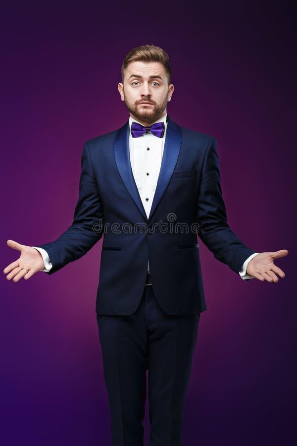 Przystojny mężczyzna w smokingu i łęku krawacie zaskakuje, rzuca jego ręki, compere w modnej, świątecznej odzieży, obraz stock