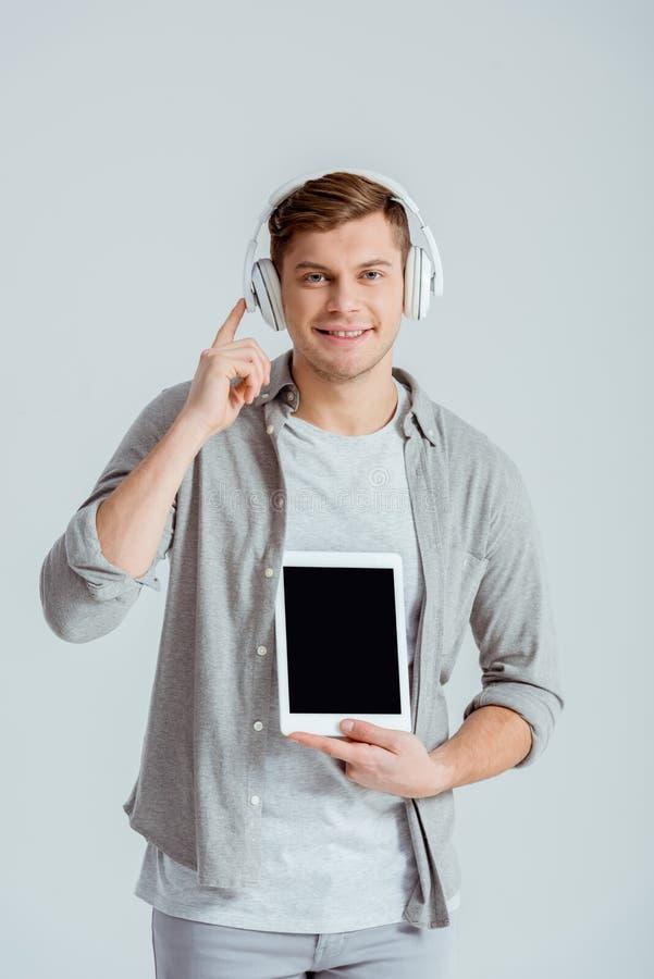 przystojny mężczyzna wskazuje z palcem przy hełmofonami odizolowywał podczas gdy trzymający cyfrową pastylkę z pustym ekranem zdjęcie royalty free