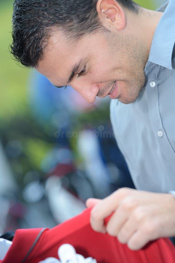 Przystojny mężczyzna wybiera koszulkę w sklepie odzieżowym obraz stock
