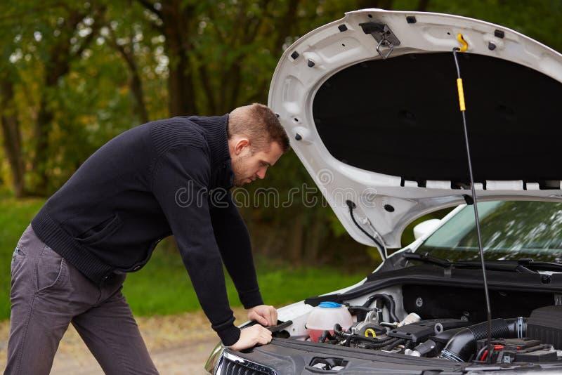 Przystojny mężczyzna z łamanym samochodem obraz stock