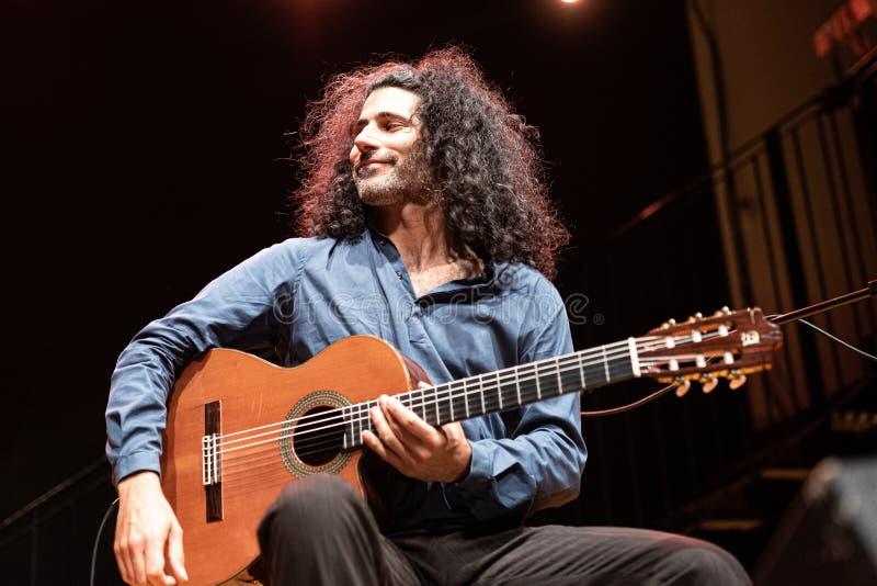 Przystojny mężczyzna z długie włosy bawić się klasyczną gitarą obrazy royalty free