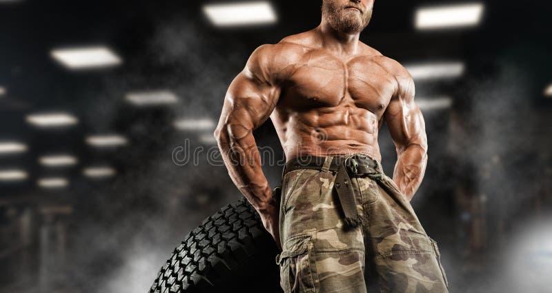 Przystojny mężczyzna z dużymi mięśniami, pozuje przy kamerą w gym zdjęcia royalty free