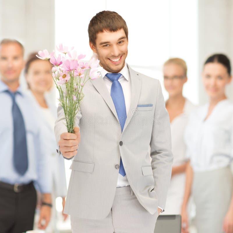 Przystojny mężczyzna z kwiatami w ręce zdjęcie royalty free