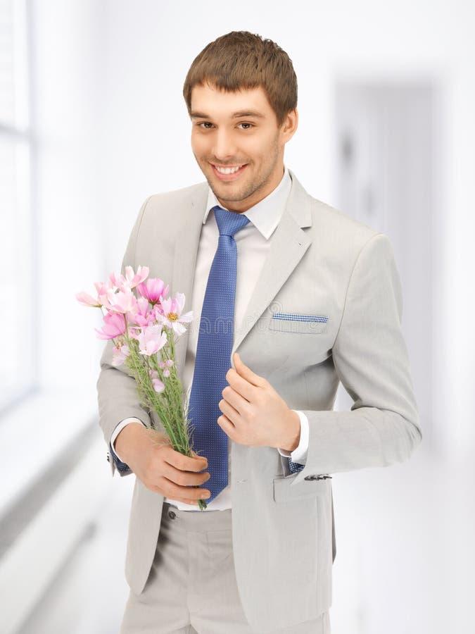 Przystojny mężczyzna z kwiatami w ręce obrazy royalty free