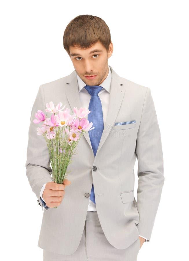 Przystojny mężczyzna z kwiatami w ręce obraz royalty free